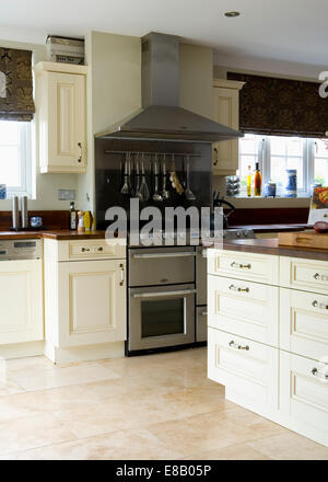 Cream travertine floor tiles in modern kitchen with large stainless steel range oven and cream fitted units