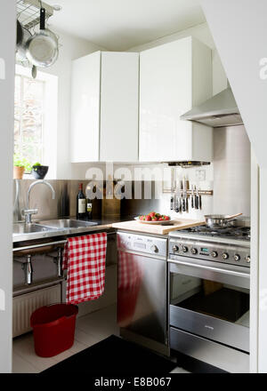 Small stainless-steel dishwasher beside stainless-steel range oven in modern white urban kitchen - Stock Photo