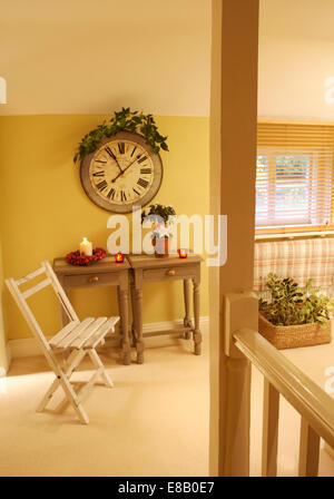 Large circular clock above two small pine tables in yellow country hall with an old white folding chair and cream - Stock Photo
