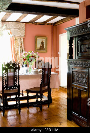 Old oak floorboards and antique Jacobean chairs in country dining room painted in Farrow & Ball Porphyry Pink - Stock Photo