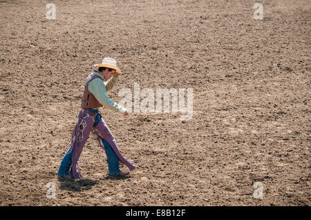 Rodeo Cowboy walking across the dirt arena. - Stock Photo