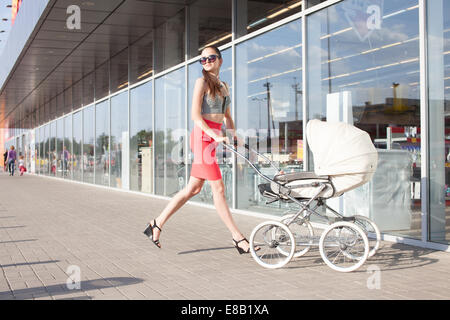 Running Trendy mother and baby in stroller - Stock Photo