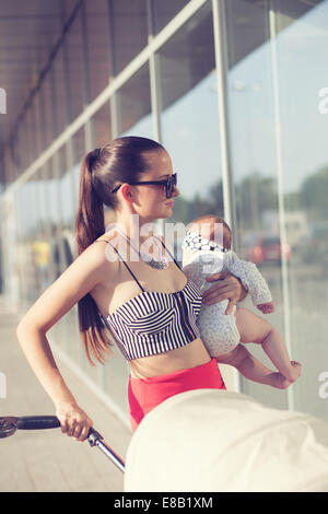 Fashionable mother and baby in arms Stock Photo