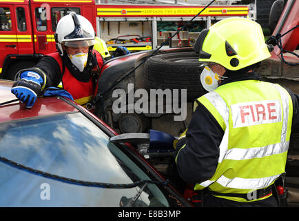 Fire service jaws of life cutting at a car crash Fire service officers cut a collision victim free from a car - Stock Photo