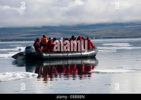 Zodia full of eco-tourists, with reflection, Baffin Island, Canada, Arctic Ocean. - Stock Photo