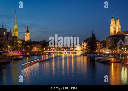 The old town of Zurich at night with the river Limmat with light trails of a waterbus, Switzerland. - Stock Photo