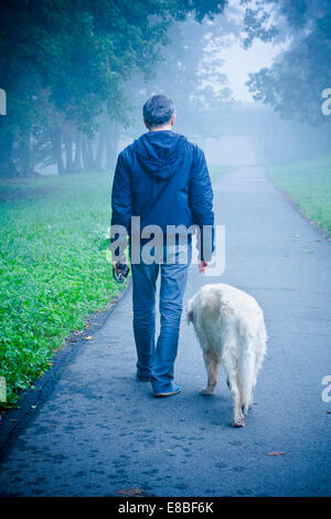 man walking with his dog in nature - Stock Photo
