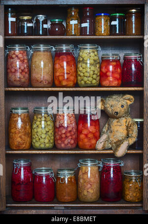 Threadbare One Eyed Teddy bear on a wooden shelf with stored bottled fruits, jams and preserves - Stock Photo