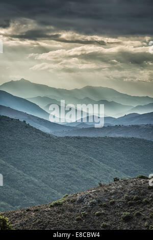 Moody skies and sunshine over receding mountains in the Balagne region of Corsica - Stock Photo