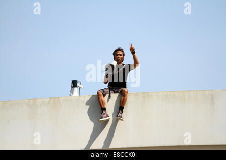 A man threatens to throw himself off a bridge during the pro-democracy protests in Hong Kong, October 2014 - Stock Photo