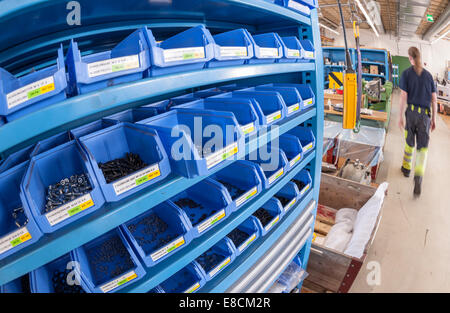 A rack filled with boxes for various nuts and bolts in a mechanical industry workshop - Stock Photo
