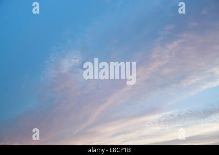 Sunlit pink clouds and blue sky at sunset - Stock Photo