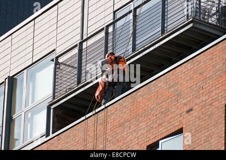 Workman using rope access technique at an apartment block, Whitworth Street, Manchester, England, UK - Stock Photo