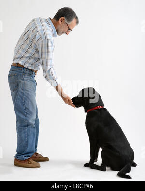 Man feeding black labrador retriever dog - Stock Photo