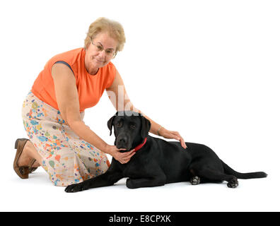 Woman petting black labrador retriever dog cut out isolated on white background - Stock Photo