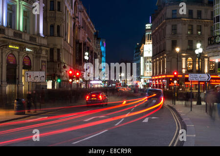 A car and black cab stop at a red light in central London making light trails - Stock Photo