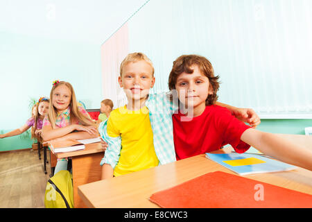 Happy boys cuddle and sit together in school - Stock Photo