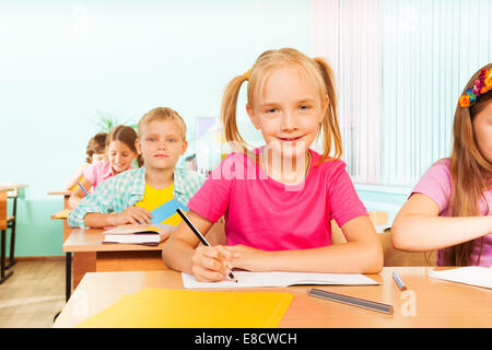 Kids sitting at table in classroom and writing - Stock Photo