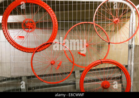 Red bicycle wheels on display at Parkour Ride a multi-discipline cycling event held in an abandoned multi-storey - Stock Photo