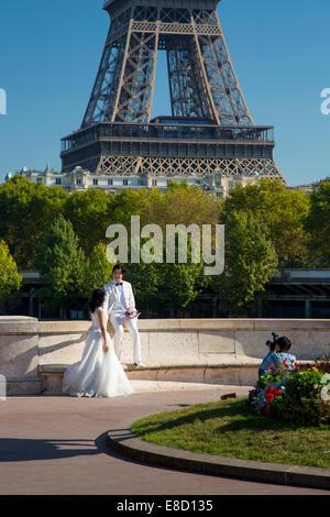 Wedding couple poses for photos below Eiffel Tower, Paris, France - Stock Photo