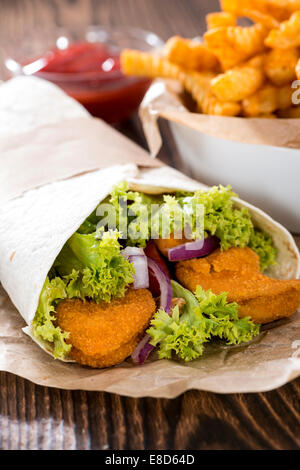 Chicken Wrap (close-up shot) with crispy fried chicken and chips - Stock Photo