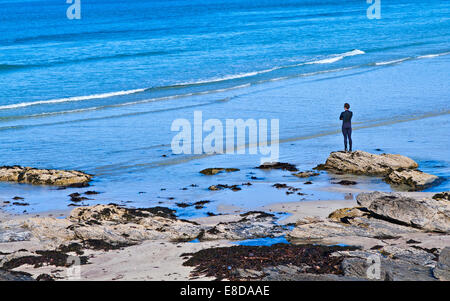 Man wearing wetsuit standing on rock at edge of sea on sandy beach looking at waves, Balnakeil Bay, Sutherland, - Stock Photo