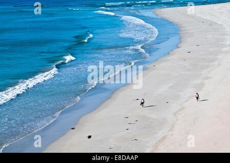 Couple walking barefoot along beautiful sandy beach at the water's edge, warm summer sunshine, Balnakeil Bay Sutherland Scotland