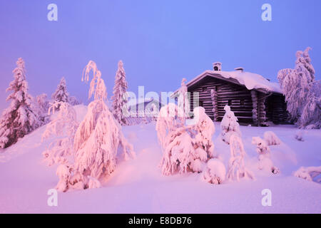 Finnish log cabin in the snow-covered landscape, Iso Syöte, Lapland, Finland - Stock Photo