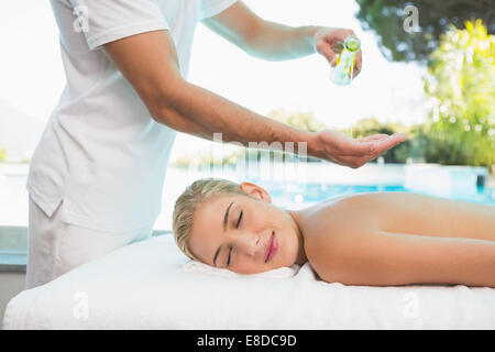 Woman receiving back massage at spa center - Stock Photo
