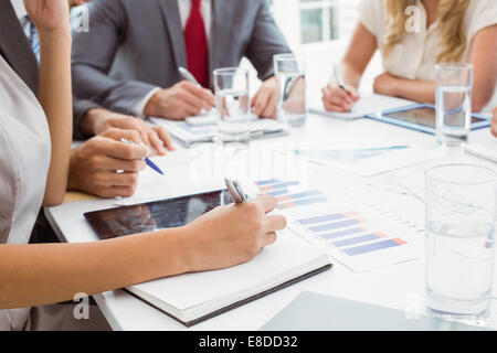 Mid section of executives writing notes in board room meeting - Stock Photo