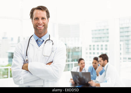 Male doctor with colleagues examining x-ray in medical office - Stock Photo