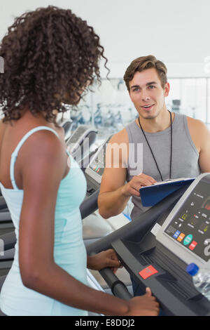 Fit woman on treadmill talking to personal trainer - Stock Photo