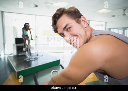 Handsome man smiling at camera in spin class - Stock Photo
