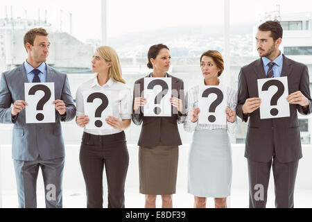 Business people holding question mark signs - Stock Photo