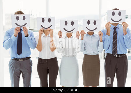 Business people holding happy smileys on faces - Stock Photo