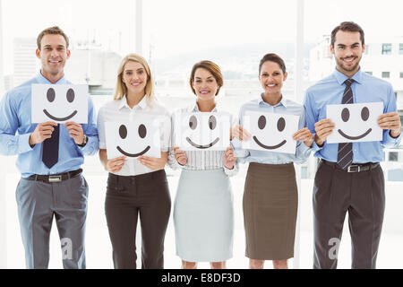 Business people holding happy smileys in office - Stock Photo