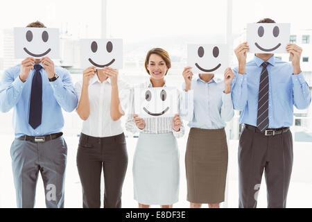 Business people holding happy smileys - Stock Photo
