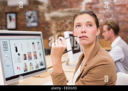 Thoughtful photo editor using computer in office - Stock Photo