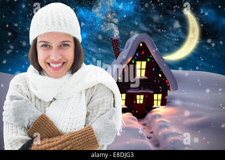 Composite image of brunette in warm clothing - Stock Photo