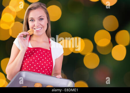 Composite image of pretty homemaker showing hot cookies - Stock Photo