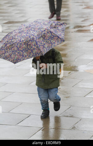 London, UK. 6th October, 2014. UK weather. Pedestrians shelter with umbrellas as they struggle with the  wet and - Stock Photo