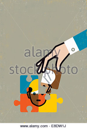Businessman's hand with missing piece of ethnic diversity jigsaw puzzle face - Stock Photo