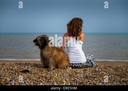 Girl and Shaggy Dog on Pebble Beach - Stock Photo