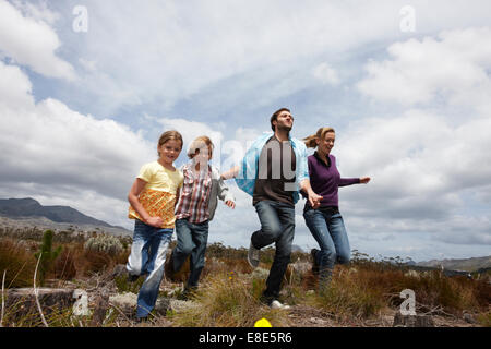 Family running in the meadow - Stock Photo