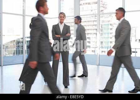 Woman standing among business people on the move - Stock Photo