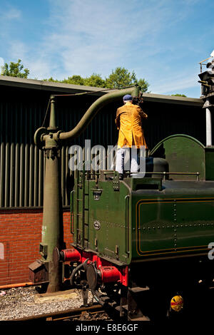 Steam train the Green Knight taking on water Pickering North Yorkshire England UK United Kingdom GB Great Britain - Stock Photo