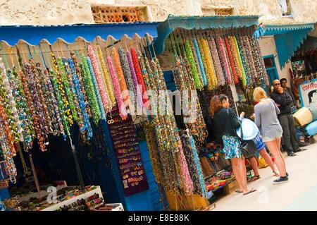 Horizontal view of Western tourists shopping in Essaouira - Stock Photo