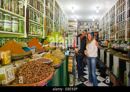 Horizontal portrait of a shopkeeper and tourist in a herb and spice shop in the souks of Marrakech.