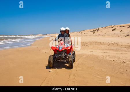 Horizontal portrait of a young man and woman on a quad bike on the beach on Morocco. - Stock Photo