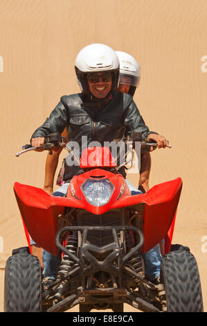 Vertical portrait of a young man and woman on a quad bike on the beach on Morocco. - Stock Photo